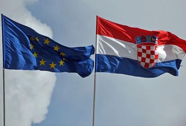 Bandeiras da União Europeia e da Croácia são vistas lado a lado em Vukovar, na Croácia, em 6 de junho. País foi integrado ao bloco europeu nesta sexta-feira (28) (Foto: Andrej Isakovic/AFP)