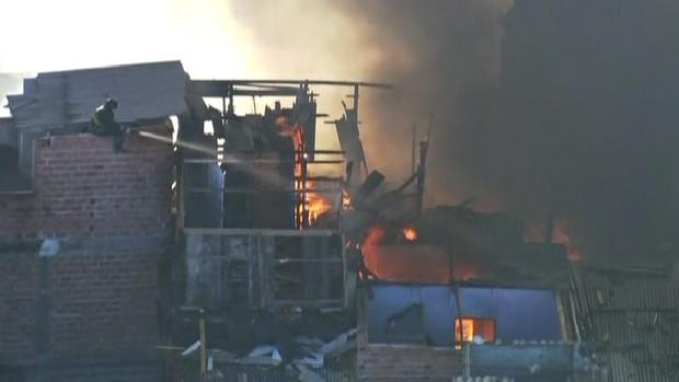 Bombeiros tentam controlar fogo em barracos (Foto: Reprodução/TV Globo)