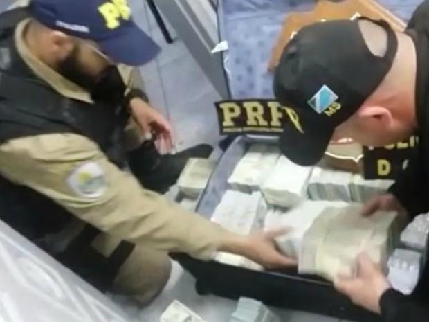 Dólares apreendidos em Corumbá estavam nas maladas dos suspeitos (Foto: PRF/Divulgação)