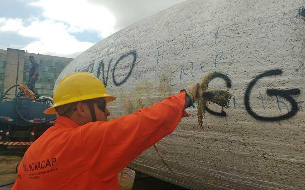 Funcionário da Novacap limpa pichação em prédio da Esplanada dos Ministérios feita durante ato contra PEC do teto de gastos na terça-feira (Foto: Elielton Lopes/G1)
