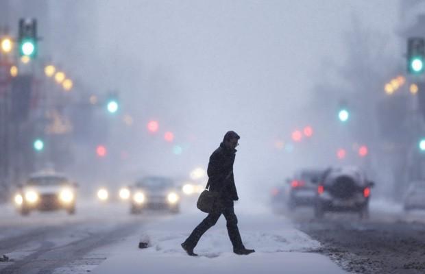 Homem atravessa a Broad Street durante tempestade de neve em Filadélfia, EUA, nesta terça-feira (21). (Foto: Matt Rourke/AP)