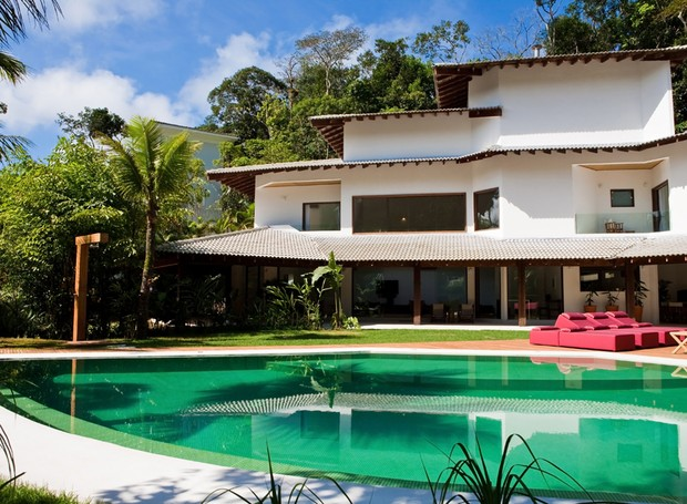 São 600 m² muito bem divididos para acomodar a família nos finais de semana em Iporanga, São Paulo. A piscina é revestida por pastilhas verde musgo da NGK. A cor foi escolhida para integrar com a paisagem ao redor que preservou as espécies nativas (Foto: Divulgação)