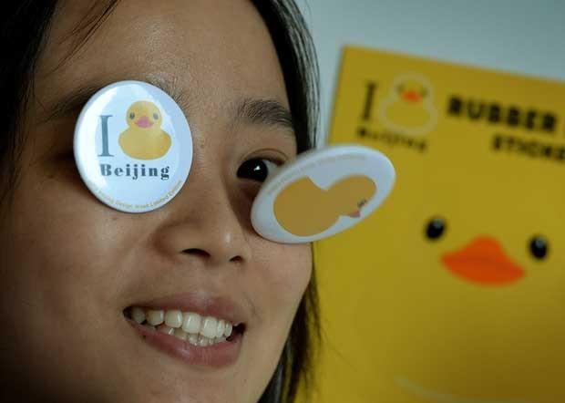 Menina chinesa exibe bottons do pato inflável em Pequim (Foto: Mark Ralston/ AFP)