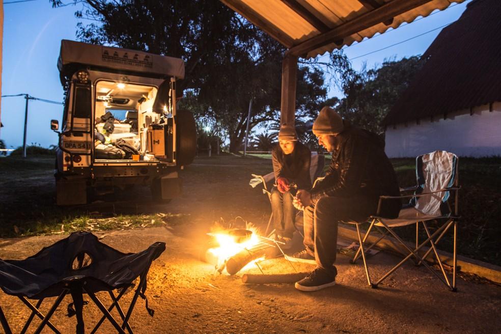 O casal se aquece em uma fogueira no Uruguai perto do carro, companheiro de viagem (Foto: Divulgação)