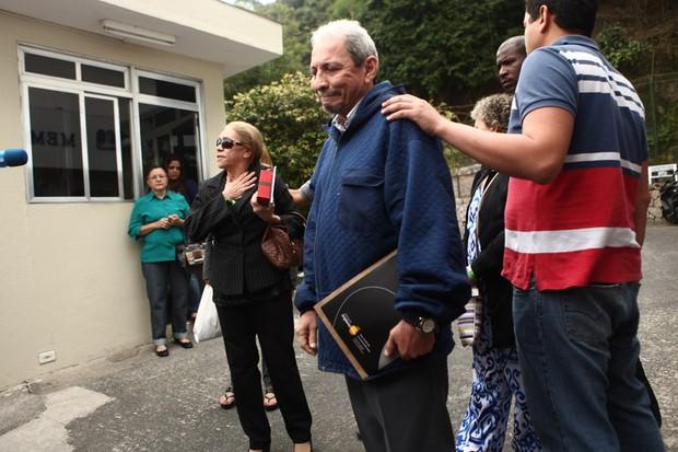 Pai e mãe de Champignon saem do sepultamento  (Foto: Iwi Onodera / EGO)