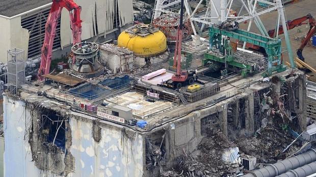 Foto aérea mostra guindaste trabalhando no reator danificado na usina nuclear em Fukushima, no Japão. (Foto: Kyodo News/AP)