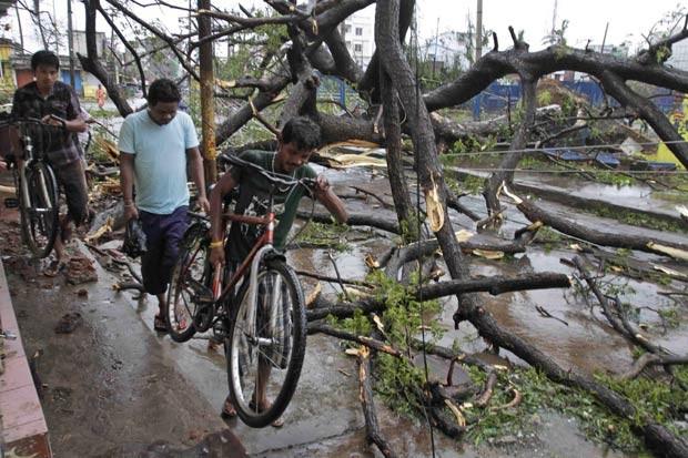 Indianos carregam suas bicicletas passando por rua onde árvores foram derrubadas pelo ciclone em Berhampur (Foto: Bikas Das/AP)