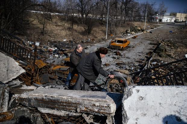 Homens empurram carrinho sobre ponte destruída de Putilovka, perto do aeroporto de Donetsk, neste domingo (21)  (Foto: AFP Photo/Dimitar Dilkoff)