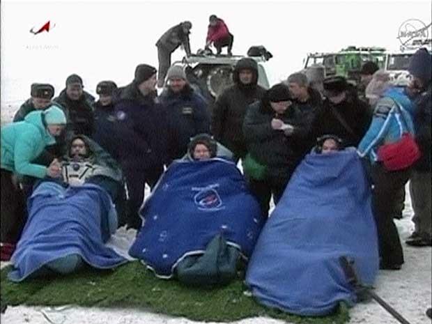 Cosmonautas russos e astronauta americano são aquecidos por cobertores logo após pouso da Soyuz nas estepes do Cazaquistão. (Foto: Nasa TV / Reuters)