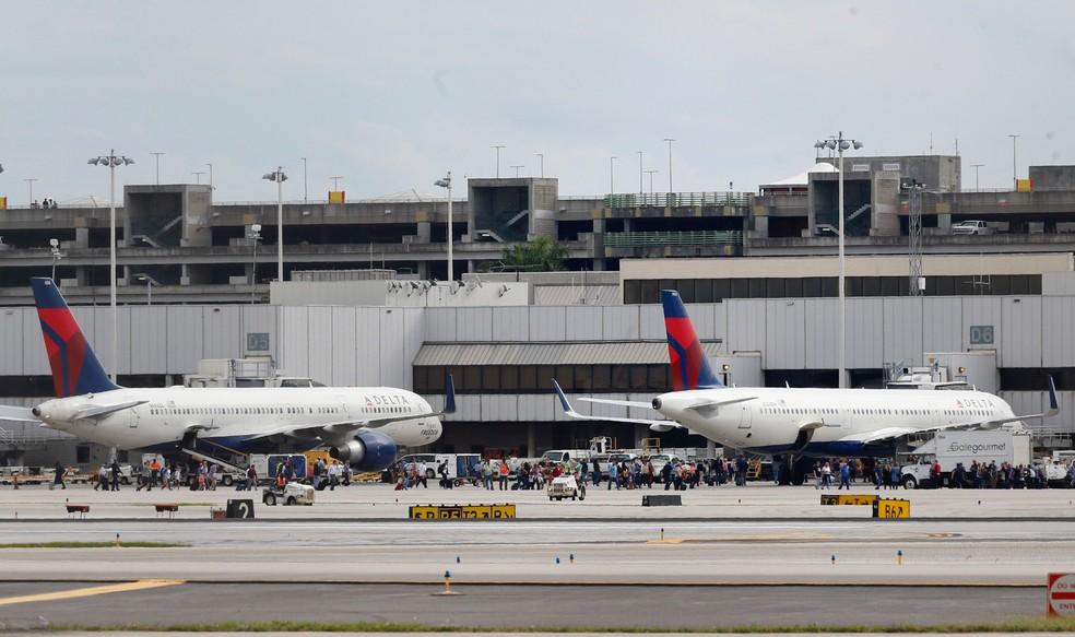 Pessoas são vistas na pista do Aeroporto Internacional de Fort Lauderdale-Hollywood, na Flórida, após um atirador abrir fogo dentro do terminal 2. Cinco pessoas morreram e oito ficaram feridas no ataque (Foto: Al Diaz/Miami Herald via AP)