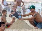 Rodrigo Hilbert brinca na areia da praia com os filhos no Rio