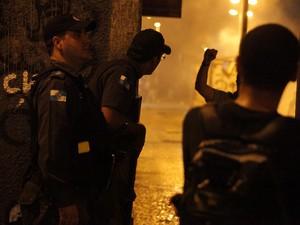 PMs tentam se proteger ao observar ação de manifestantes no Centro do Rio (Foto: Rodrigo Gorosito/G1)