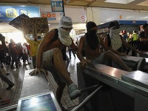 Manifestantes mascarados usam os pés para forçar e quebrar catracas da estação de metrô durante protesto no Rio (Foto: André Mourão/Agência O Dia/Estadão Conteúdo)