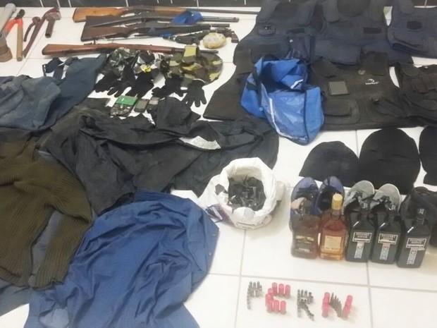 Foram apreendidos durante a operação: armas de fogo de uso restrito, munições, explosivos, dinheiro, coletes balísticos, grampos, blusões, coturnos e até garrafas de uísque (Foto: Polícia Civil/Divulgação)