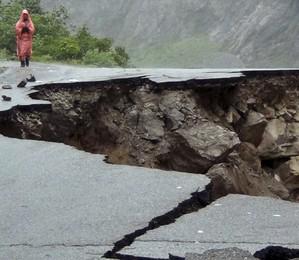 Parte de estrada desaba após forte chuva no estado de Uttarakhand, no norte da Índia.  Ao menos 23 pessoas morreram e dezenas estão desaparecidas em decorrência de inundações e deslizamentos de terra que acontecem na região nos últimos dias (Foto: AP Photo)