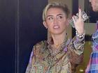 De shortinho, Miley Cyrus dá abaixadinha para apagar cigarro