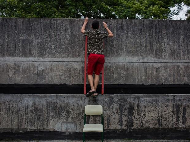 Estudante sobe em muro da entrada da Escola Estadual Caetano de Campos (Foto: Victor Moriyama/G1)