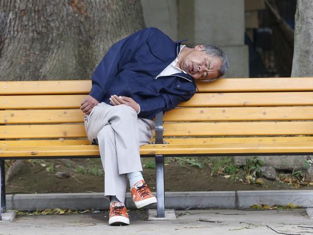 Homem tirou soneca desajeitada em banco em Tóqui, no Japão (Foto: Shizuo Kambayashi/AP)