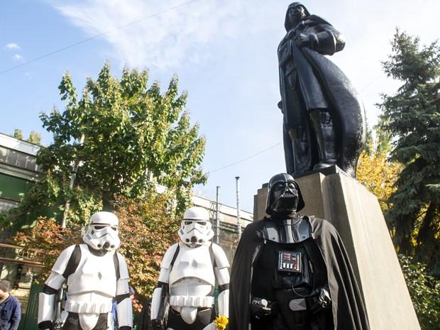 Pessoas vestidas como personagens de 'Guerra das Estrelas' posam ao lado de estátua de Darth Vader em Odessa, na Ucrânia, na sexta (23) (Foto: AFP Photo/Volodymyr Shuvayev)