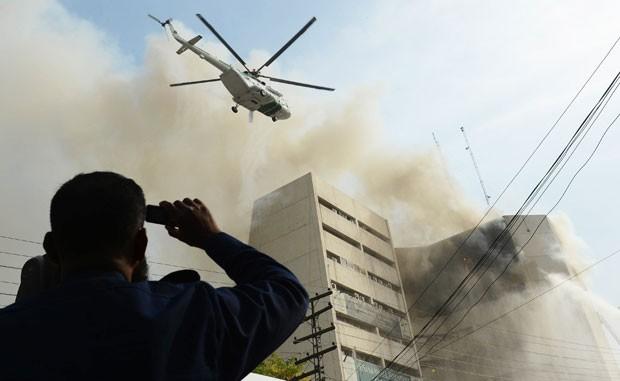 Helicóptero é usado em resgates no edifício em chamas em Lahore (Foto: Arif Ali/AFP)
