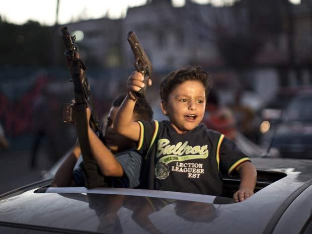 Crianças segurando armas participam das comemorações pelo acordo de cessar-fogo duradouro nesta terça (26) na cidade de Gaza (Foto: AFP PHOTO/MAHMUD HAMS)