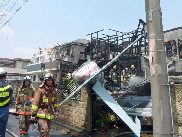 Bombeiros tentam controlar as chamas após avião de pequeno porte cair em área residencial perto de Tóquio (Foto: REUTERS/Kyodo)