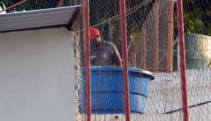 Funcionário do Boa Esporte retira a bola de dentro da caixa d'água (Foto: Tiago Campos)