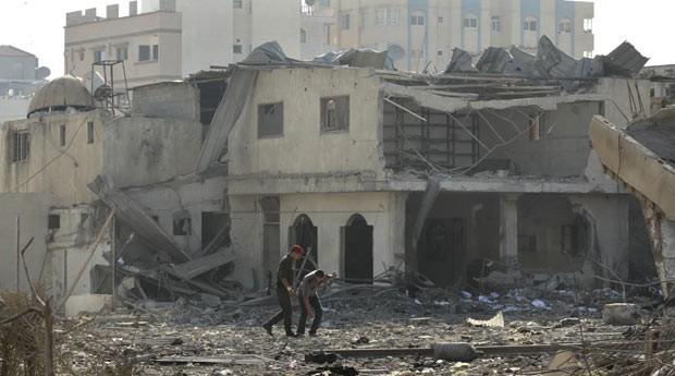 Militantes palestinos em frente a posto do Hamas atingido por bombardeio na cidade de Gaza neste sábado (23) (Foto: AFP)