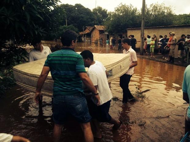 Homens ajudam a carregar colchão após água invadir casa do setor Jardim Querido, em Porto Nacional (Foto: Alexandre Alves/TV Anhanguera)