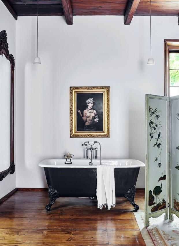 Banheira. No canto do quarto, o espaço para um banho relaxante é uma deliciosa indulgência. O retrato barroco é parte da série African Hospitality, de Andrew Putter, filmada em Babylonstoren (Foto: Greg Cox / Bureaux)