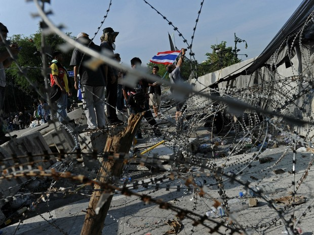 Manifestantes diante de barricada policial parcialmente desmontada diante da sede do Governo da Tailândia. (Foto: Christophe Archambault/AFP)