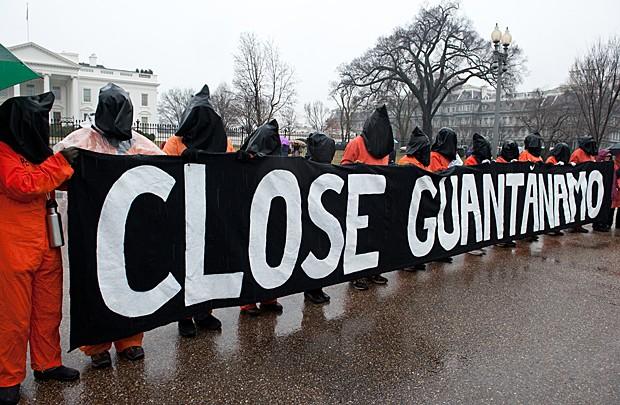 Manifestantes com macacões alaranjados de presidiários e capuzes pretos seguram faixa que pede 'Fechem Guantánamo', em frente à Casa Branca, em Washington D.C., neste sábado (11) (Foto: Nicholas Kamm/AFP)