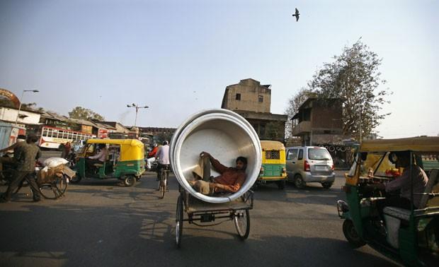 Um homem foi flagrado nesta sexta-feira (8) viajando dentro de uma panela enorme que era transportada por um triciclo riquixá em uma estrada movimentada na cidade de Ahmedabad, na Índia (Foto: Amit Dave/Reuters)