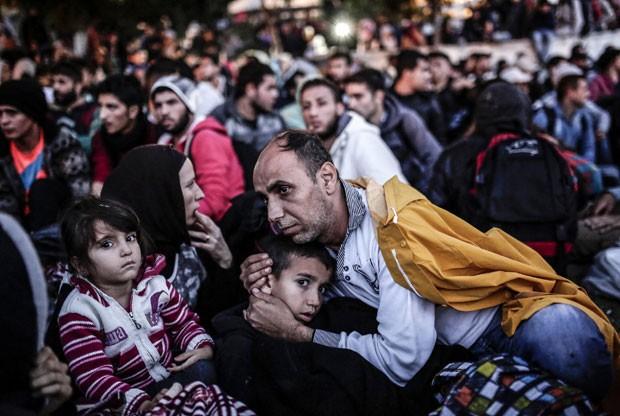 Migrantes e refugiados esperam por ônibus para ir até a fronteira da Turquia com a Grécia nesta quarta-feira (16), após passarem a noite acampados (Foto: Yasin Akgul/AFP)