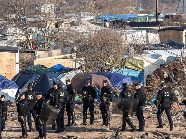 Policiais são vistos no local onde estão sendo desmontadas as barracas de migrantes no acampamento 'A selva', em Calais, na quarta (20) (Foto: AFP Photo/Philippe Huguen)