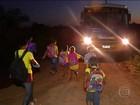 Crianças caminham no escuro para pegar o transporte escolar em MS