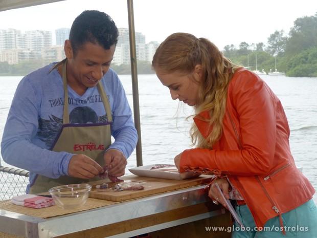 Angélica observa atentamente as habilidades de MC Leozinho na cozinha (Foto: Estrelas/TV Globo)