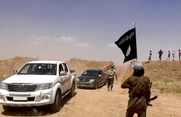Militantes do Estado Islâmico do Iraque e Síria, um grupo terrorista ligado à al-Qaeda, removem barreira que separa a fronteira síria-iraquiana. Grupo controla território nos dois países (Foto: AP)