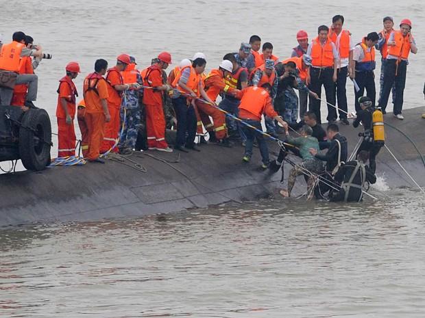 Sobrevivente do naufrágio do navio de cruzeiro Estrela do Oriente é retirado do rio Yangtze em Juanli, na China. A embarcação naufragou com 458 pessoas a bordo, todas chinesas, segundo autoridades. Mais de 400 pessoas foram dadas como desaparecidas (Foto: AFP)