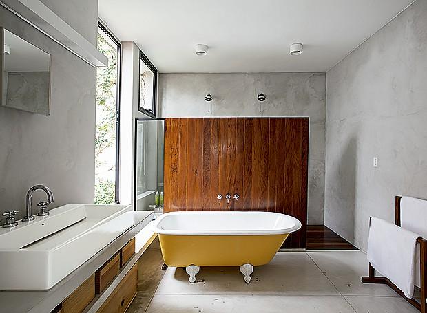 Área de banho: o painel de madeira de demolição, executado pela Mie Marcenaria, separa banheira e boxe com duchas Deca (Foto: Gui Morelli/ Editora Globo)