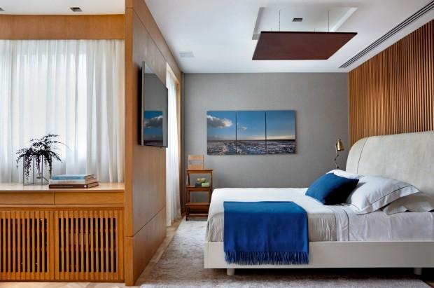 A cama da Artefacto, com roupa da Trousseau, fica diante de um painel ripado de tauari tonalizado e sobre tapete de algodão da Casa Julio (Foto: Denilson Machado / MCA Estúdio)