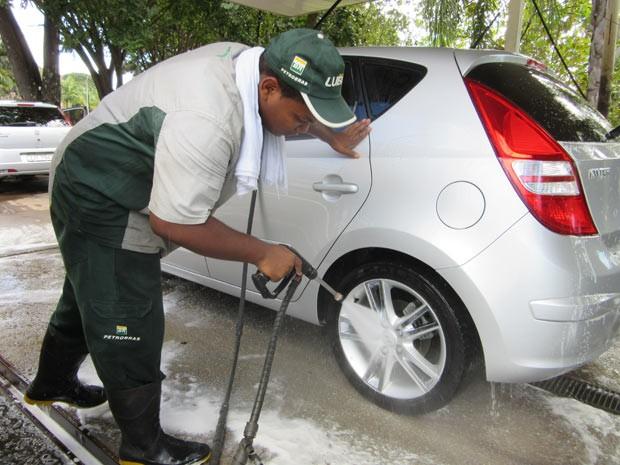 Funcionário de lava-jato que oferece 'seguro-chuva' em Brasília, durante o serviço (Foto: Raquel Morais/G1)