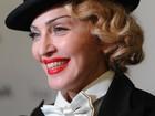 Com look masculino, Madonna vai a première com dente sujo de batom