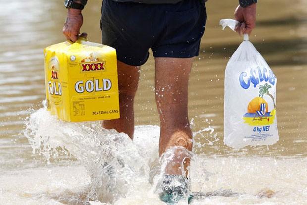 Em janeiro de 2011, um homem foi visto andando em uma rua alagada em  Rockhampton, Queensland, na Austrália, enquanto carregava uma caixa de cerveja e gelo (Foto: Reuters)