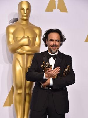 O diretor mexicano Alejandro González Iñárritu segura três das quatro estatuetas vencidas por 'Birdman' no Oscar 2015 (Foto: Jordan Strauss/Invision/AP)