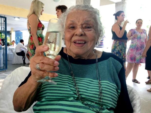 Dona Glorinha com champanhe na mão comemorando os 100 anos (Foto: Lara Gilly/G1)
