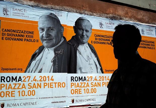 Cartazes anunciam a canonização dos papas João XXIII e João Paulo II no Vaticano (Foto: Filippo Monteforte/AFP)