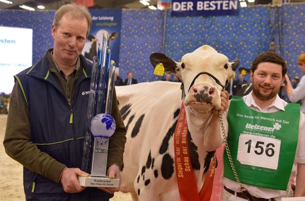 Alex Dittmer (esq) segura trofeu após sua vaca 'Ornella' vencer concurso (Foto: Carmen Jaspersen/AFP)