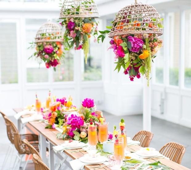 Ambiente externo ou interno? Um pouco dos dois! Pendure arranjos de flores coloridas ao contrário, usando cestas de palha como suporte, e use as mesmas plantas e cores na decoração da mesa. Almoço com cara de verão e cheio de graça!  (Foto: Reprodução/Pinterest)