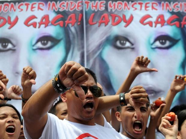 Membros do grupo Biblemode Youth Philippines protestam em frente a cartaz de show de Lady Gaga, neste sábado (19) (Foto: AFP)